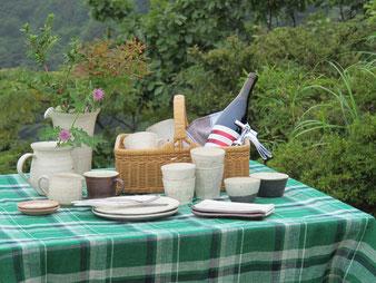 屋外の緑豊かな公園にアウトドア用のテーブルが置いてあり、食事をするために食器やかごやワインが乗っている