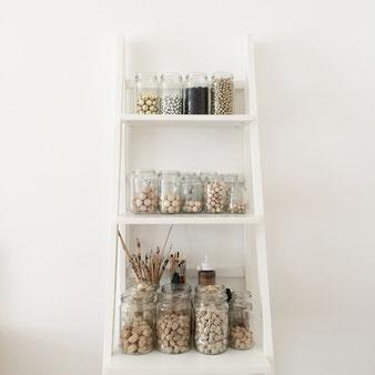 Regal mit Behältern für Holzperlen