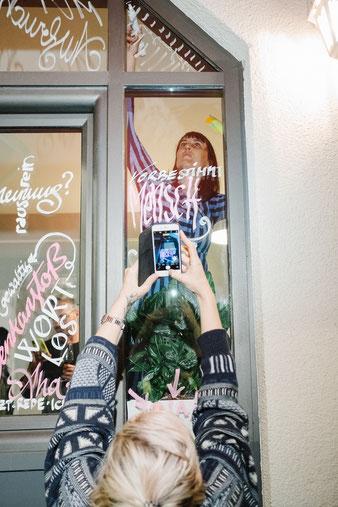 Dijana Hammans kalligrafiert die Worte ihrer Gäste auf das Schaufenster vom Café DA