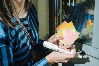 Dijana Hammans hält die auf Postits festgehaltenen Assoziationen zu den Bildern in Händen. Dijana Hammans kalligrafiert die Worte ihrer Gäste auf das Schaufenster vom Café DA