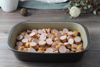 Currywurst in Stücken geschnitten in die Ofenhexe von Pampered Chef verteilen