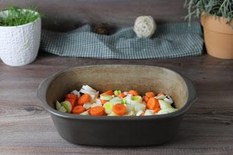 Suppengemüse kleinschneiden und in den Ofenmeister legen