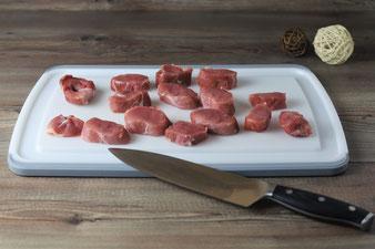 Fleisch mit dem Kochmesser auf dem großen Schneidebrett mit Saftrillen in Medaillons schneiden