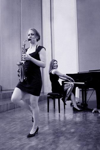 Zwei elegant gekleidete Musikerrinen mit Saxophon und Flügel