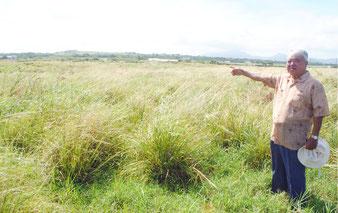 旧陸軍白保飛行場跡地を指す石垣繁さん。現在は一面の平野。