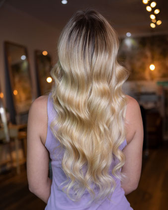 Weft extensions in blonde hair for added length ad volume