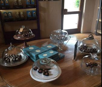 Hazel Mountain Chocolates Tisch mit verschiedenen Parlinen auf Tellern unter Glasglocken