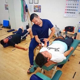 野球肘の治療。二人は痛みが同じでも原因は別々。奥の子は肩関節や胸郭などの柔軟性不足によるフォームが悪いことが原因。手前の子は肘から前腕の筋や筋膜の癒着が強く、ケア方法などが原因。