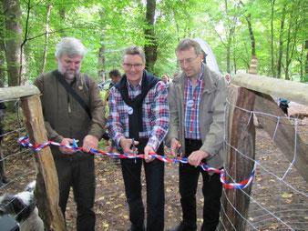 (v.li.) Knut Sturm vom Stadtwald Lübeck, Senator Bernd Möller und Holger Lindberg vom Hunde-Freilauf-Lübeck zerschneiden das Eröffnungsband.