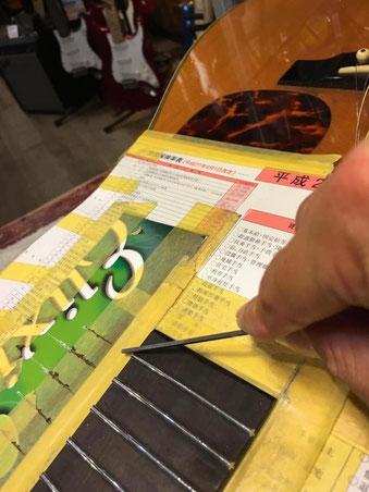 ギターのネックに新しいステンレスフレットをつけている作業のアップ