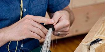Für die Bogenbehaarung wird die richtige Haarmenge sorgfältig abgemessen.