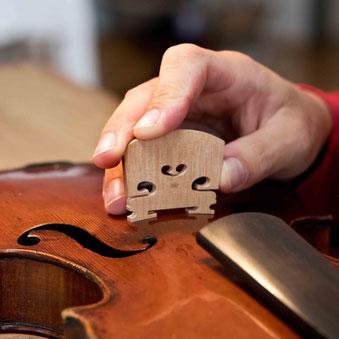 Der Steg wird exakt an die Form der Geigendecke angepasst.