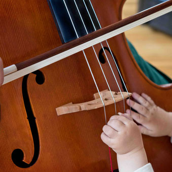 Diese Babyhände sind noch zu klein, um ein Cello zu spielen.