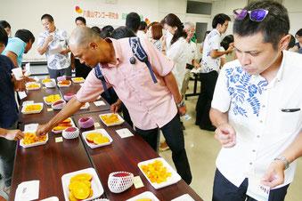 八重山のマンゴーをA試食する県職員ら=26日、県八重山合同庁舎