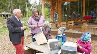Foto: H. Rauscher: Die Kinder des Waldkindergartens spielen begeistert in und um ihr neues Blockhaus. (v. li: Helmut Rauscher, Daniela Idzik-Neumann)