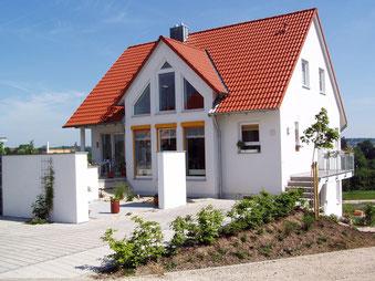 Einfamilienhaus mit weisser Fassade  und rotem Steildach