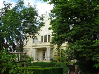 Villa hinter großen alten Bäumen