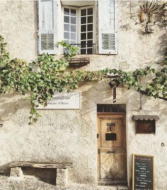 südländische Hausfassade mit Weinreben bewachsen, kleiner Holzsitzbank und einladender Haustür