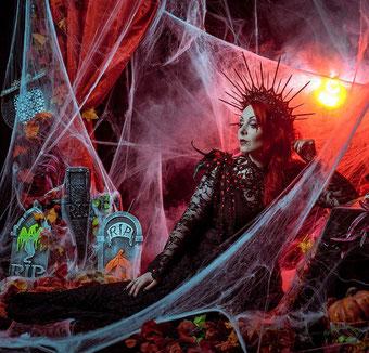 Halloween Gothic Model mit rotem Collier und Flügeln in Spinnweben und Grabkulisse