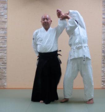 ④取りの手首伸側が受けの同名側の手首屈側に結び、同側の足は膝を地に着けると共に母指先を真下の地に結ぶ。