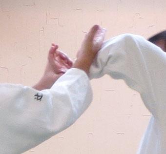 ⑧右手は手背の分だけ入って受けの腕に結ぶ・入り身に続く転換で開いた側頸へ受けの左手母指球を結ぶ