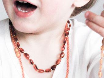 Kleinkind Ausschnit vom Oberkörper mit Bernsteinketten