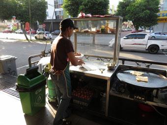 店先でロティーを焼くミャンマー人の青年。
