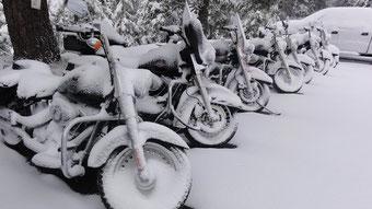 7 Verschneite Motorräder auf einem Parkplatz