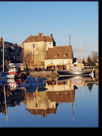 """L'ancien port de Honfleur, appelé Vieux Bassin, en hiver, avec le marché de Noël et une décoration """"igloo et ours polaire"""" au milieu du bassin"""