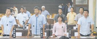 安保法案の今国会での成立を求める意見書に起立して賛成する与党議員=14日午前、石垣市議会