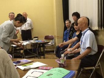☆集合写真撮影。手前の白いシャツの男性がご担当者。その向う黒いシャツの方が館長さん。館長さんが右手に持っておられるのはiPhoneについているイヤホーンのリモートスイッチ。このスイッチがシャッターになります。