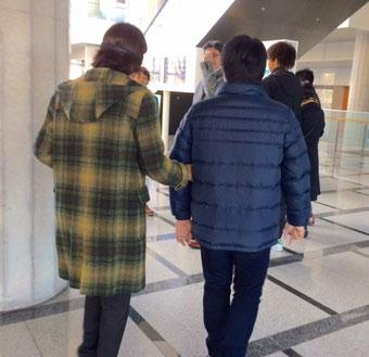 ☆国際会議場から外に出かけるところ。写真左側がアイマスクをして歩いています。右側のサポートさんの左腕を触っています。
