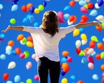 風船を背景に手を広げる女性