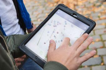 Teamevents in München: Ein Mann hält beim Geocaching ein Tablet und orientiert sich in der Stadt
