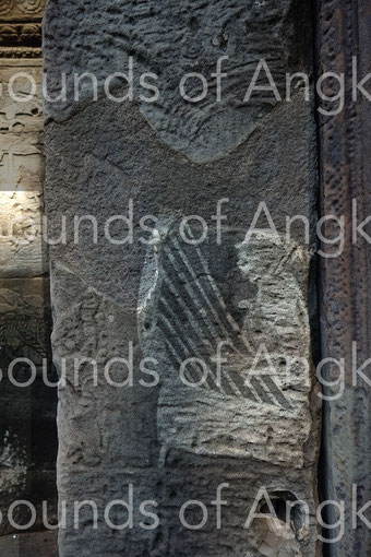 Harp on a Bayon's pilaster played by a woman. A foot is visible.