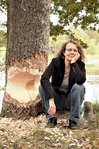 Das Bild zeigt die Autorin Daniela Schenk, die an einem See sitzt.