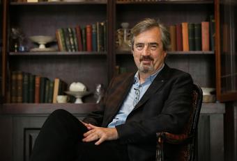 Das Bild zeigt den Autor Sebastian Barry vor einem Bücherregal sitzend.