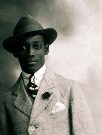 Das Bild zeigt den Autor Anton de Kom mit Anzug und Hut.