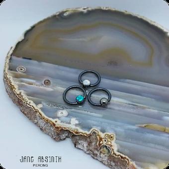 Drei Niobium Ringe mit Opalstein als Piercingschmuck für Septum, Helix im Piercingstudio bei Jane Absinth in Düsseldorf. Schmuck von Precision One Jewelry.