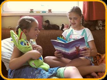 Kinder spielen mit Stoffpuppe, lesen Tjupi-Büchlein