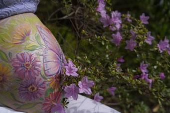 Ein silbern schimmernder rosa Schmetterling sitzt auf vielen rosa-orange-gelben Blüten. Foto im Garten vor einer blühenden violetten Azalee.