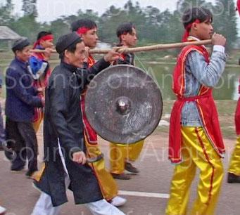 Gong processionnel chez les Kinh du Vietnam. Le musicien tient le lien en V renversé afin de limiter l'oscillation du l'instrument.