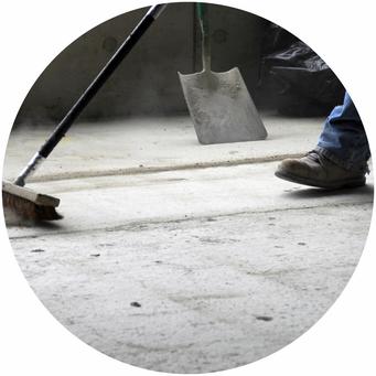 Baureinigung, Mann beseitigt Dreck mit Besen