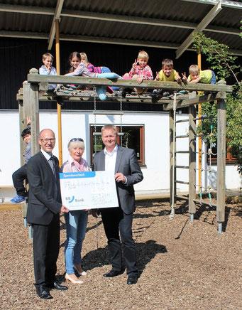 Bei der Spendenübergabe: Stefan Kunz, Barbara Itschner und Thomas Birkenmaier (v.l.) vor dem Klettergerüst mit Kindern