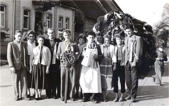 Sickinger Kerweburschen und ihre Mädchen beim Gasthaus zum Bahnhof ca. 1956. In der Mitte Kurt Sauter mit Kerwekuchen und Reiner Banghard mit Krug