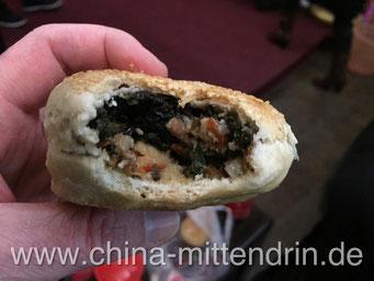 So sieht ein Guangbing von innen aus: gefüllt mit Gemüse und Fleisch. Der Geschmack erinnert entfernt an Grünkohl oder Wirsinggemüse, nur eben leicht gesüßt.