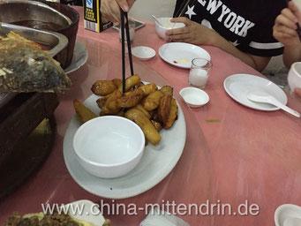 Man greift sich ein Stück Süßkartoffel mit den Stäbchen, dabei zieht die noch heiße Zuckerglasur Fäden (Ba Si).