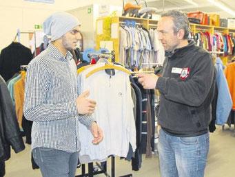 Der neue Lotse für Flüchtlinge Wael Hamid (rechts) aus Syrien erklärt einem Besucher des Sozialkaufhauses die Abkäufe in der Einrichtung. Foto: Dießelkämper