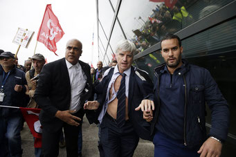 Security officers escort AF's Pierre Plissonnier away, after workers invaded Air France offices - courtesy Bloomberg