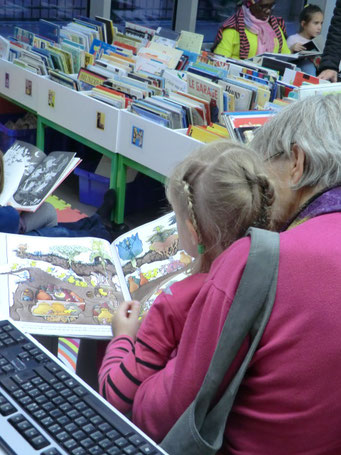 Photo d'un adulte lisant un album à un enfant au Biblio-Club
